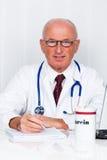 Arzt in der Praxis mit Stethoskop und Laptop. Stockfoto