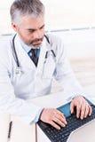 Arzt für Allgemeinmedizin bei der Arbeit Stockbild