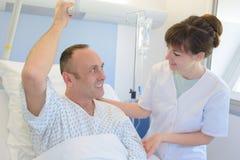 Arzt mit dem Patienten, der im Bett wieder herstellt Lizenzfreies Stockfoto