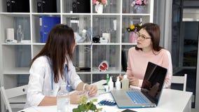 Arztdermatologenbüro macht Empfehlungen brunette weiblichen Patienten Frauen existiert in der medizinischen Uniform stock video