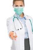 Arztfrau in der Maske, die Spritze zeigt Stockbild