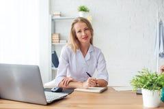 Arztfrau, die am Schreibtisch in medizinischem sitzt stockbild