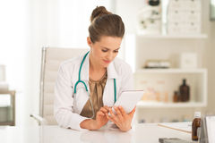 Arztfrau, die Tabletten-PC verwendet Stockbild