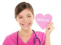 Arzthelferindoktor, der GESUNDHEITS-Zeichen auf Herzen zeigt Stockfotografie