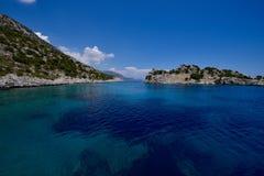 As águas claras do mediterrâneo de uma baía em Grécia Imagens de Stock Royalty Free