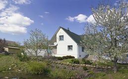 As árvores de maçã de Blossomig aproximam a lagoa da vila Foto de Stock