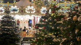 As árvores de Natal decoram a cidade No fundo fora do carrossel de gerencio do foco, em que as crianças montam festive video estoque