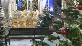 As árvores de Natal decoram a cidade No fundo fora do carrossel de gerencio do foco, em que as crianças montam festive filme