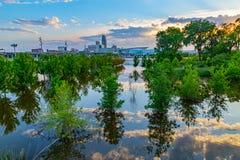 As árvores, o céu e as reflexões das nuvens no Conselho do parque da borda do rio inundado de Tom Hanafan blefam Iowa foto de stock