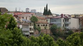As árvores verdes em Tbilisi estacionam, construções no monte, arquitetura do capital Georgian vídeos de arquivo