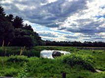 As Above, So Below. Rural landscape reflects the cloudy sky above in the placid pond water below Stock Photos