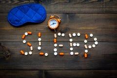 As ajudas da medicina obtêm adormecidas Bom sono Exprima o sono alinhado com máscara e o despertador próximos do sono dos comprim imagens de stock