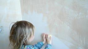 As ajudas da menina para fazer reparos em sua sala A criança pinta as paredes com um rolo video estoque