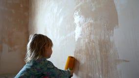As ajudas da menina para fazer reparos em sua sala A criança pinta as paredes com um rolo filme