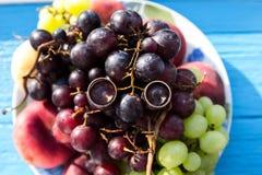 As alianças de casamento, alianças de casamento no fruto chapeiam o close up Foto de Stock Royalty Free