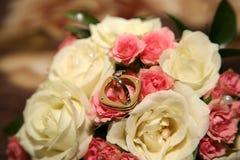 As alianças de casamento do ouro encontram-se em um ramalhete das rosas Imagens de Stock Royalty Free