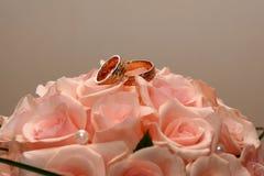 As alianças de casamento do ouro encontram-se em um ramalhete das rosas Imagem de Stock Royalty Free