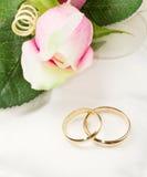 As alianças de casamento do ouro no descanso branco com aumentaram Imagem de Stock