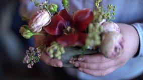 As alianças de casamento do ouro são introduzidas dentro de uma flor vermelha bonita filme