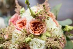 As alianças de casamento douradas encontram-se em um botão da rosa do rosa Mentira das alianças de casamento em uma flor em botão Fotografia de Stock