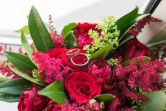 As alianças de casamento douradas encontram-se em um botão da rosa do vermelho Mentira das alianças de casamento em uma flor em b Fotografia de Stock Royalty Free