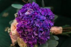 As alianças de casamento douradas no ramalhete da hortênsia roxa, rosas cor-de-rosa florescem com as fitas lilás no estilo rústic fotos de stock