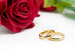 As alianças de casamento e artificial aumentaram no fundo branco Foto de Stock