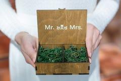 As alianças de casamento em uma caixa de madeira encheram-se com o musgo na grama verde Imagens de Stock Royalty Free