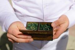 As alianças de casamento em uma caixa de madeira encheram-se com o musgo na grama verde Fotografia de Stock Royalty Free