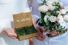 As alianças de casamento em uma caixa de madeira encheram-se com o musgo na grama verde Fotografia de Stock