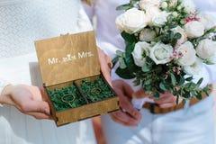 As alianças de casamento em uma caixa de madeira encheram-se com o musgo na grama verde Imagens de Stock