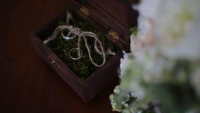 As alianças de casamento em uma caixa de madeira encheram-se com o musgo na tabela A caixa de madeira com alianças de casamento e Fotografia de Stock Royalty Free