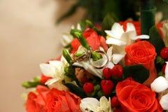 As alianças de casamento encontram-se em um ramalhete da noiva Fotos de Stock