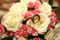 As alianças de casamento encontram-se em um ramalhete da noiva Foto de Stock Royalty Free