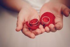 As alianças de casamento encontram-se nas palmas das crianças com as pétalas das rosas Imagens de Stock