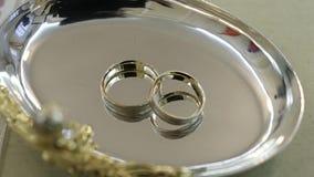 As alianças de casamento estão em uns pires do metal vídeos de arquivo