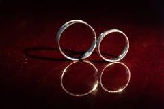 As alianças de casamento são suporte um o fundo vermelho Fotografia de Stock Royalty Free