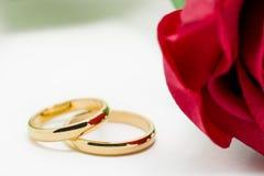 As alianças de casamento e artificial aumentaram no fundo branco Fotografia de Stock
