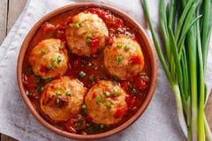 As almôndegas da galinha com molho de tomate em uma argila rolam imagens de stock royalty free