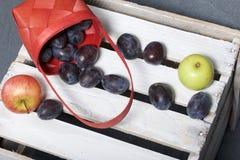 As ameixas e as maçãs perfumadas maduras desintegraram-se fora de uma cesta de vime Localizado em uma caixa de madeira, batida fo foto de stock royalty free