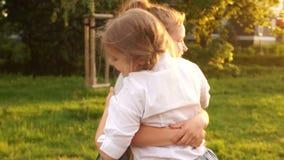As amigas adolescentes abraçam e riem no fundo da luz solar, infância feliz, feriados de escola, retrato exterior vídeos de arquivo
