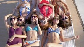 As amigas alegres com corpos 'sexy' nos maiôs estabelecem ao mesmo tempo na espreguiçadeira e no riso filme