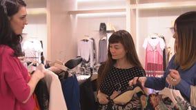 As amigas bonitas das meninas na loja escolhem a roupa video estoque