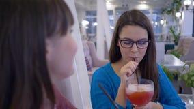 As amigas de sorriso no divertimento dos monóculos dizem e bebem o suco através da palha durante o jantar no restaurante em féria vídeos de arquivo