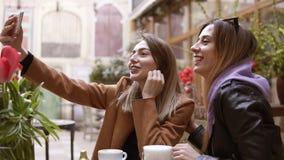 As amigas fazem o selfie na câmera do telefone celular ao sentar-se em um café duas meninas atrativas tomam imagens na c?mera filme
