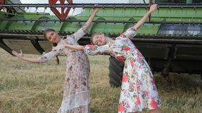 As amigas flexíveis do aldeão em vestidos longos têm o divertimento perto do trator no campo vídeos de arquivo