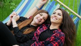 As amigas lésbicas encontram-se na rede no jardim Abraço e riso da mulher de duas lésbica vídeos de arquivo