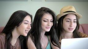 As amigas novas bonitas olham o portátil, sorrindo e tendo o divertimento que senta-se em um bar filme