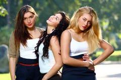 As amigas novas e bonitas têm o divertimento no parque Imagens de Stock Royalty Free