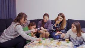 As amigas novas passam o tempo de lazer junto em casa e comendo o sushi video estoque